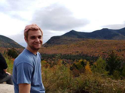 A young man standing outdoors with a beautiful landscape behind