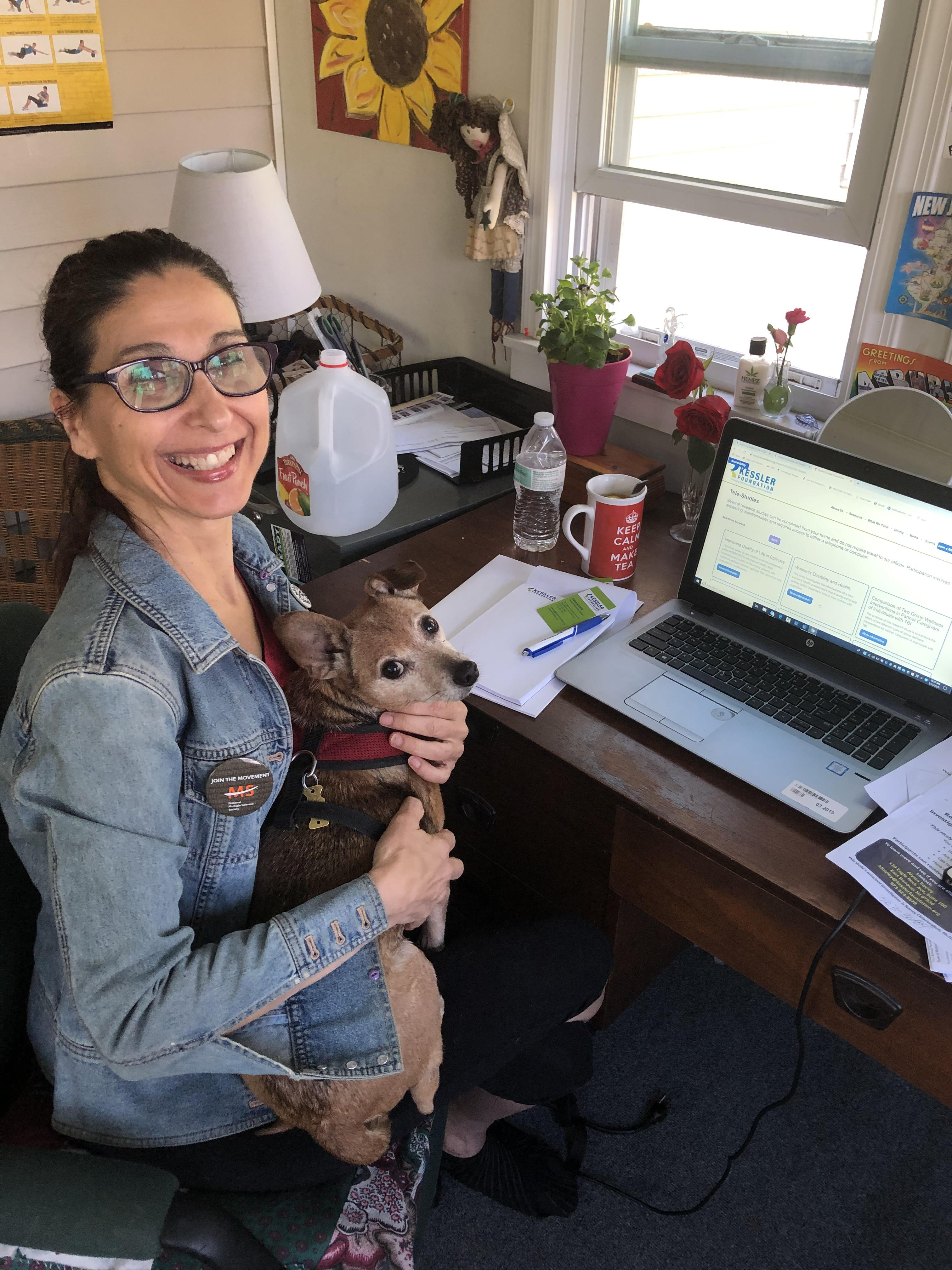 Carla Basante holding her dog, smiling at the camera, and working from home