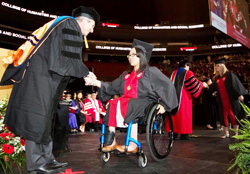 woman in a wheelchair accepting diploma from a man