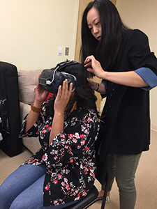 Woman putting on VR headset with help from another woman