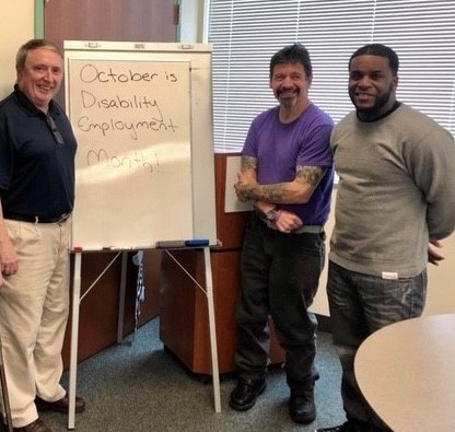 Three men smiling and standing next to a white board with text
