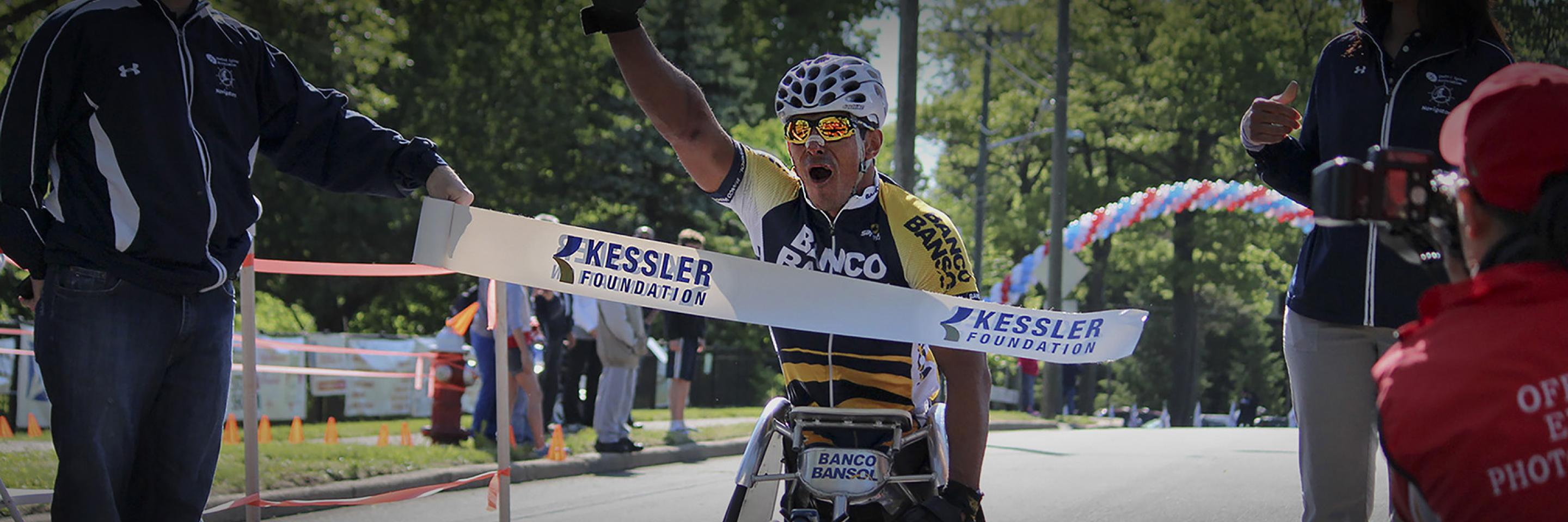 Ridgewood Wheelchair Bike Race Winner crossing finish line