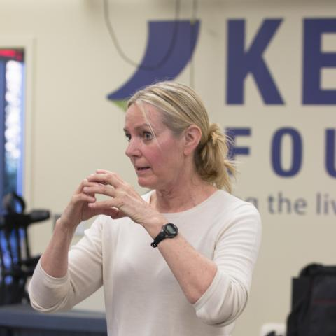 Dr. Gail Forrest using her hands to demonstrate while giving a speech