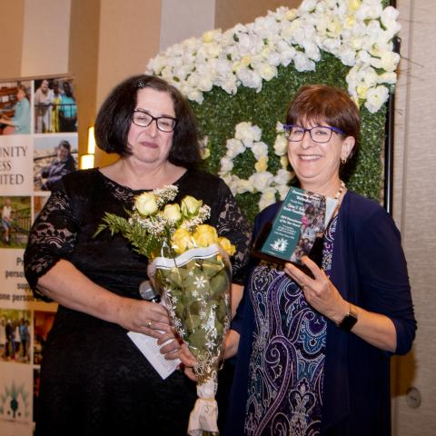 Photo of Elaine Katz holding her award and standing next to a woman.