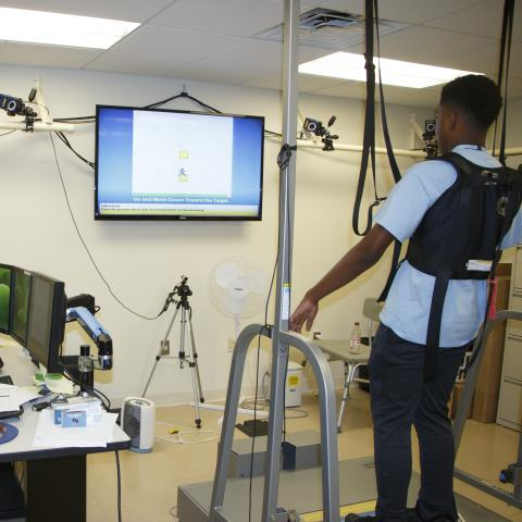 Two people in a science lab testing out balance equipment