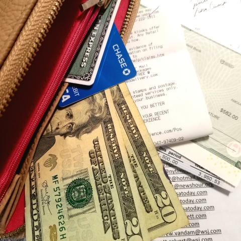 Photo of a purse and money and receipts scattered