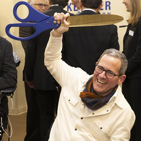 Tim Reynolds holding up big ceremonial scissors at Center for Spinal Stimulation ribbon cutting