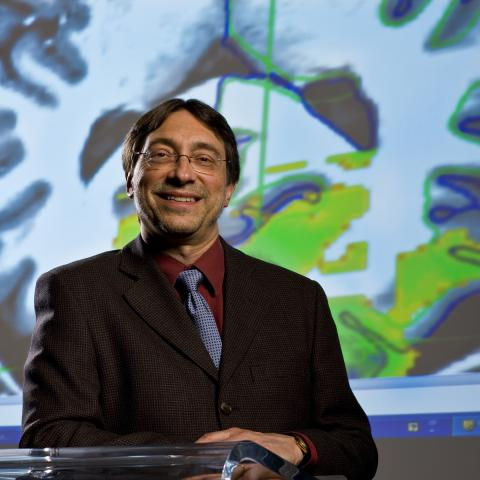 Dr. John DeLuca with brain image in background