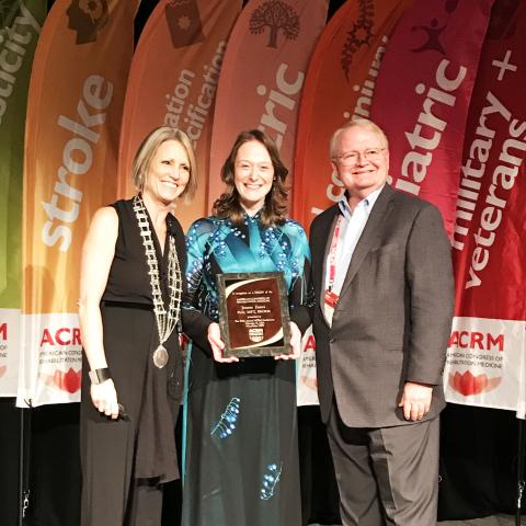 Dr. Jeanne Zanca receiving award at ACRM and standing with a male and female