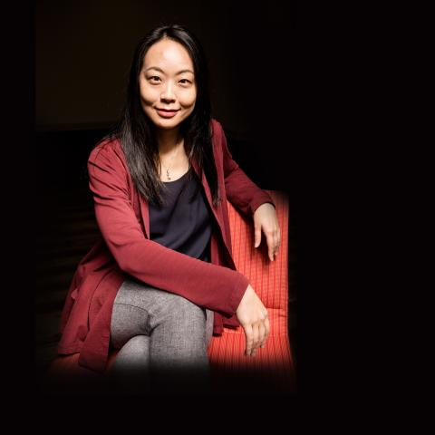 Dr. Peii Chen sitting on a chair against a black background