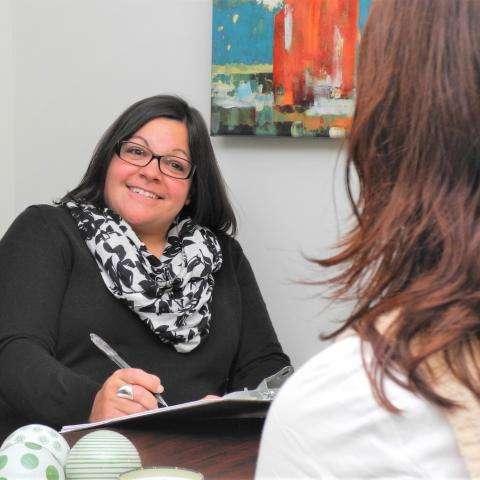 Photo of Dr. Lauren Strober, holding a pen and notepad while talking to patient