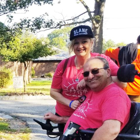 Photo of a man in a wheelchair and a woman standing next to him