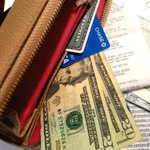 Wallet with credit cards, money and receipts scattered