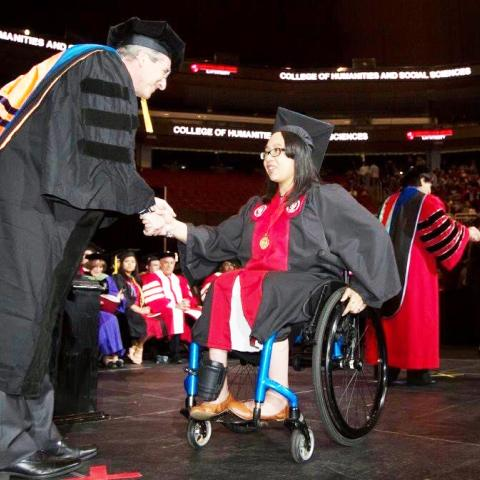A graduate in a wheelchair on stage, receiving her diploma and shaking hands with a man