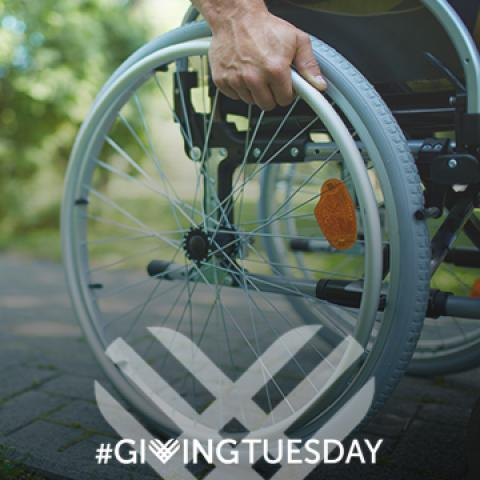 Wheelchair user with Giving Tuesday logo