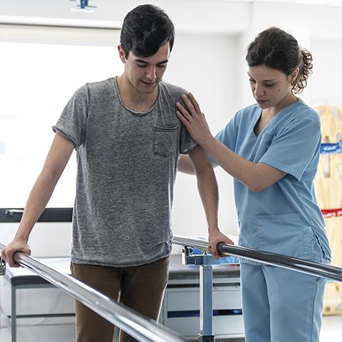 Nurse helping man walking using parallel bars