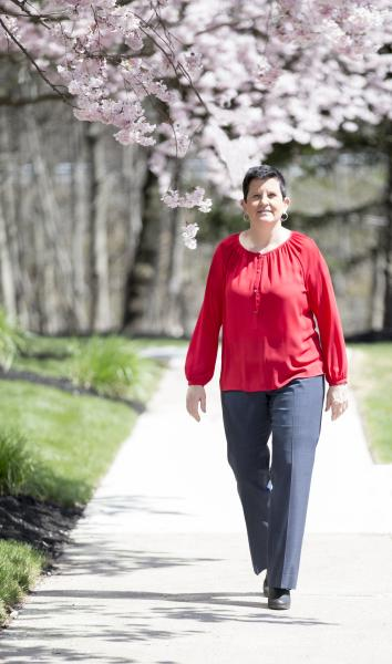 Angela Smith, Person in red shirt walking next to cherry blossom tree, smiling at camera, cancer survivor