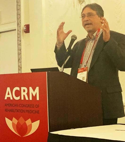 Photo of Dr. John DeLuca presenting at the ACRM conference
